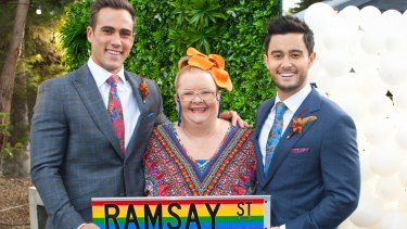 Rainbow over Ramsay Street: Magda Szubanski (Jemima Davies-Smythe) helps Matt Wilson (left, Aaron Brennan) and Tayaka Honda (David Tanaka) tie the knot.