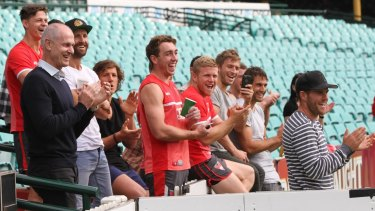 Sydney Swans players and coaching staff give Alex Johnson a standing ovation as he completes his lap.