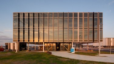 Mirrat's new office at Web Dock designed by Plus Architecture. The simple tinted glass Miesian box elevated on pilotis is Australia's first 6-star green star facility of its kind.