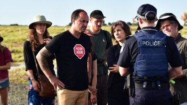 Greens MPs Jeremy Buckingham and Dawn Walker and protesters confront Queensland Police during an anti-Adani protest on Wednesday.