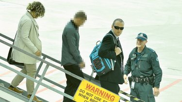 Police take Brodie Wild, left, from a plane which arrived at Melbourne Airport from the Gold Coast on Sunday.