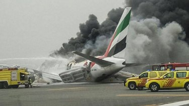 Crews work to extinguish a fire on Emirates flight EK521 after it was involved in an accident.