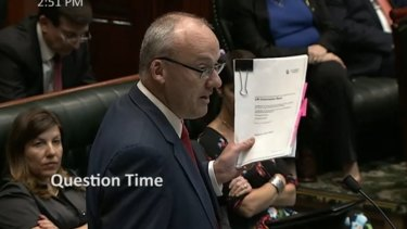 Opposition leader Luke Foley lifts a leaked copy of the land titles registry privatisation contract during Question Time on Thursday.