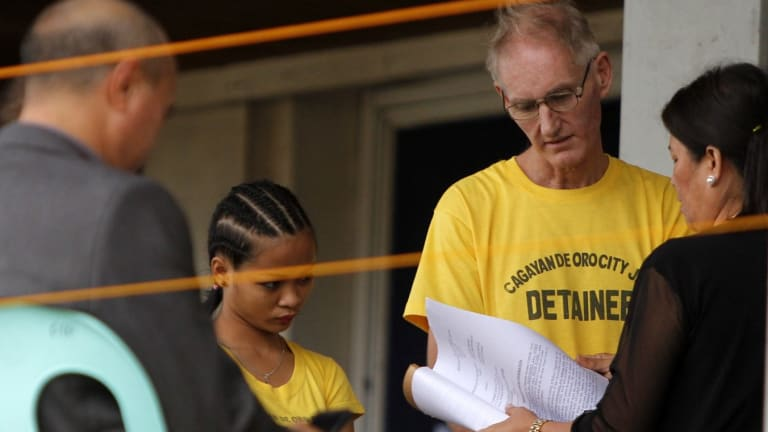 Alleged paedophile Peter Gerard Scully, 52, and his former live-in partner Carmen Ann Alvarez (left, both in yellow shirts) are arraigned in Cagayan de Oro on Tuesday.