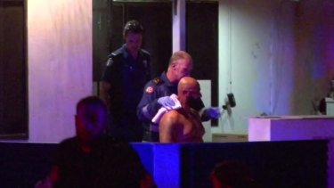 Radwan Zraika, the first victim of three western Sydney shootings in March, being escorted to an ambulance.