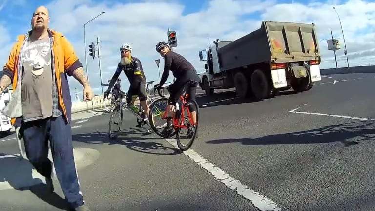 The truck driver confronts the cyclist at the scene.