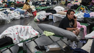 People displaced by flooding rest at a temporary shelter at the George R. Brown Convention Center in Houston.