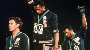 Tommie Smith (centre), and John Carlos (right) salute after winning gold and bronze at the 1968 Olympics.