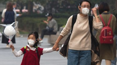 Health a risk: A woman and child wear masks during a hazy day in Beijing.