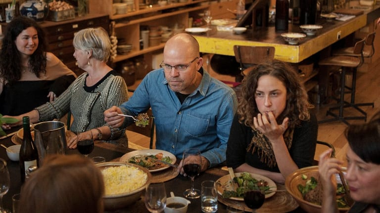 Smart Urban Villages director Rolf von Behrens (centre) hosts a community dinner in the WestWyck communal kitchen to launch the new village project.