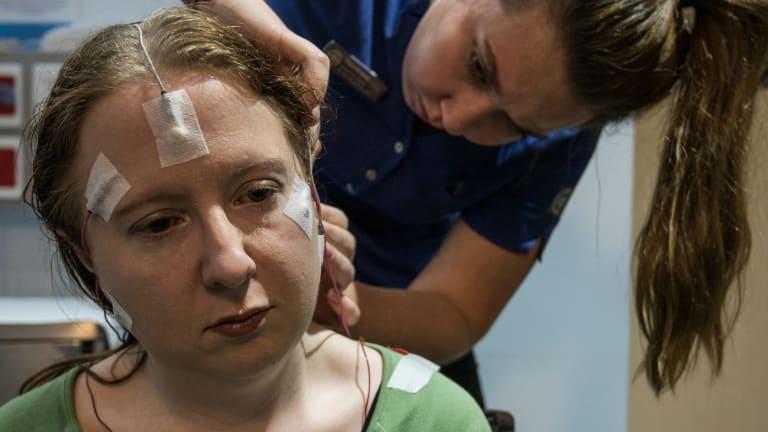 Sleep technologist Ciara Holland prepares Kathrin Bain for her overnight sleep study.