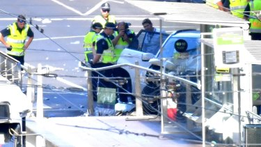 Police inspect the car at the scene of the incident.