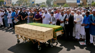 Thousands gather to pray at caskets of Imam Maulama Akonjee, draped in green top, and Thara Uddin.