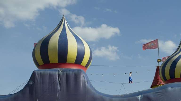 The Great Brokovski aka Ashley Brophy of the The Moscow Circus  walking the tightrope between peaks of the big top.