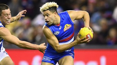 Jason Johannisen of the Bulldogs is chased by Nathan Hrovat of the Kangaroos during the round 14 AFL match between the Western Bulldogs and the North Melbourne.