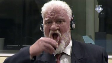 Slobodan Praljak brings a bottle of poison to his lips during a Yugoslav War Crimes Tribunal in The Hague.