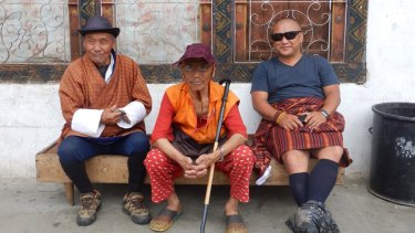 Men sit outside a house in downtown Paro, Bhutan.
