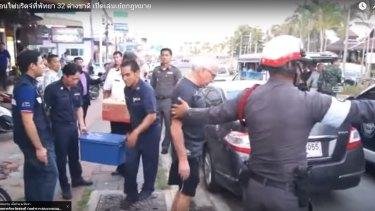 An elderly bridge player is arrested by a Thai policeman in Pattaya.