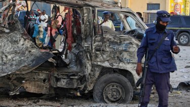 Security forces stand near the wreckage of a minibus at the scene of a car bomb attack in Mogadishu last month.