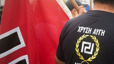 A protester wearing a Golden Dawn T-shirt, next to a swastika flag in Brisbane.