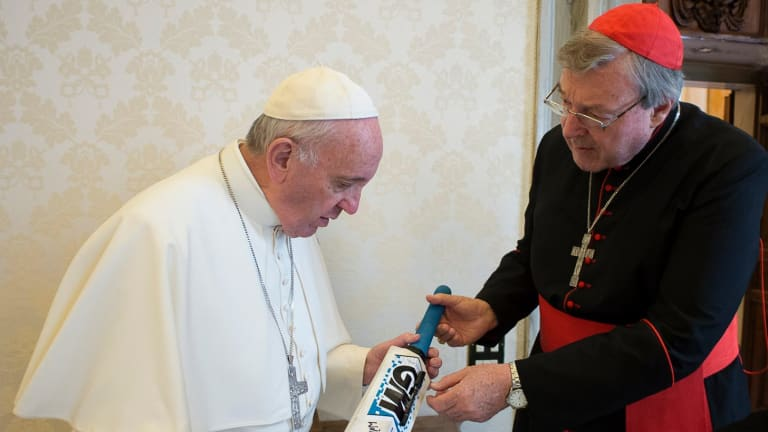Pope Francis receives a cricket bat from Cardinal George Pell at the Vatican in 2015.