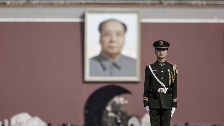 A member of the People's Armed Police stands guard in front of a portrait of former Chinese leader Mao Zedong at Tiananmen Gate in Beijing. China has indicated a continued slowdown in defence spending growth this year, as President Xi Jinping presses ahead with a sweeping military overhaul.