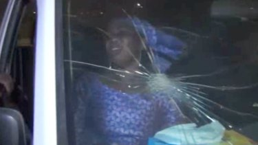 A rescued woman sits in a vehicle with bullet hole in its windshield near the Splendid Hotel in Ouagadougou.