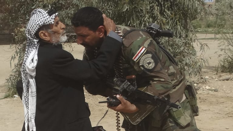 Thank you: A man kisses an Iraqi soldier after security forces pushed out Islamic State terrorists from villages outside Ramadi, Iraq, on Wednesday.