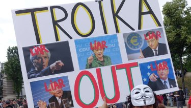 """A man holds a sign that reads """"Troika Out""""  in Paris."""