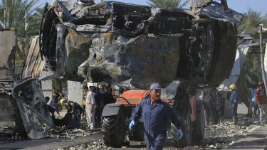 War still evident in Iraq: Civilians and security forces gather as municipality workers remove destroyed vehicles at the scene of a deadly suicide bomb attack in Hillah, about 95 kilometres south of Baghdad.