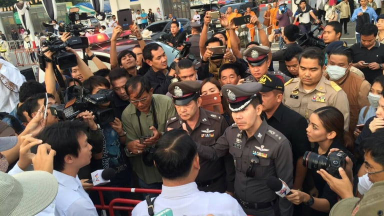 A media scrum forms around senior police at the temple.
