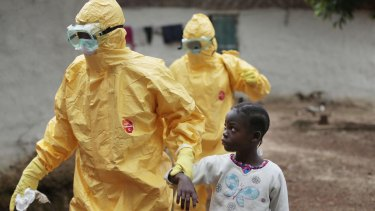 A young girl is taken to an ambulance after showing signs of the Ebola infection in Liberia during the 2014 outbreak.