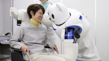Robear lifts a woman into a wheelchair during a demonstration in Nagoya, Japan.