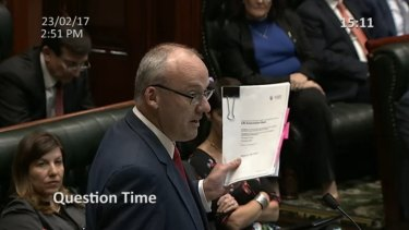 NSW Opposition leader Luke Foley holding a leaked copy of the LPI concession deed during Question Time in February.