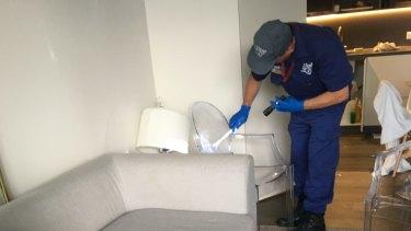 Police go through the apartment.