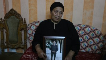 Fayza Makeen holds a portrait of her husband Magdy Makeen, who died in police custody, at their home in the Cairo district of al-Zawiya al-Hamra.