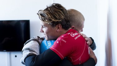 Julian Wilson (in red) hugs Mick Fanning, who was attacked by a shark during the fInal of the J-Bay Open on Sunday.