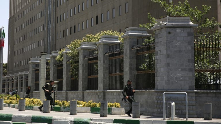 Police officers run to take position around Iran's parliament building following an assault by several attackers on Wednesday.