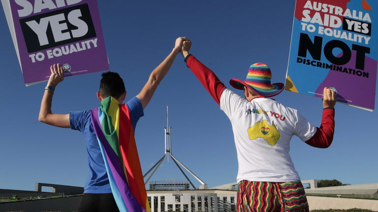 Supporters of same-sex marriage pose for photographers with the rainbow flag during a rally on the front lawn of Parliament.