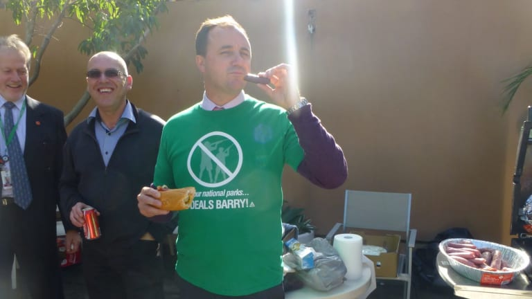 """NSW Greens MP Jeremy Buckingham eats a """"freshly-hunted"""" sausage at a barbecue in 2013."""
