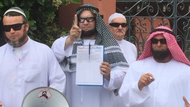 Nick Folkes (pictured left) and fellow representatives from the Party For Freedom protest outside Malcolm Turnbull's home.