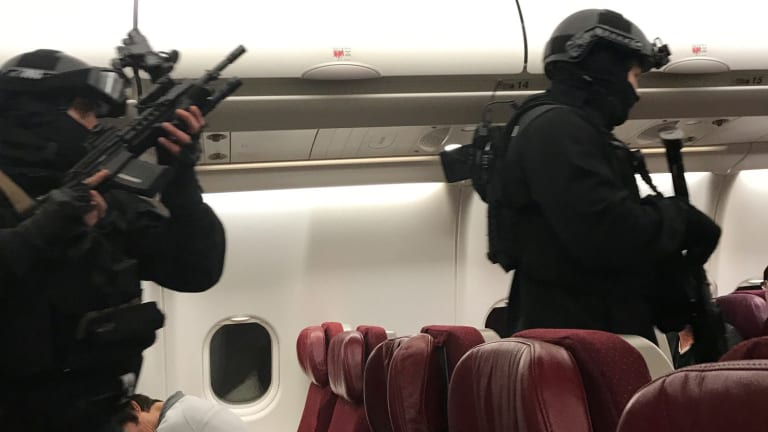 Heavily armed police enter the plane.