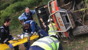 Emergency services help the woman as she remains trapped in the overturned RTV.