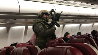 Security personnel board Flight MH128 after it returned to Melbourne.