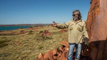 Senior cultural ranger at Murujuga National Park, Jakari Togo, looks out to sea next to rock carvings on the Burrup Peninsula.