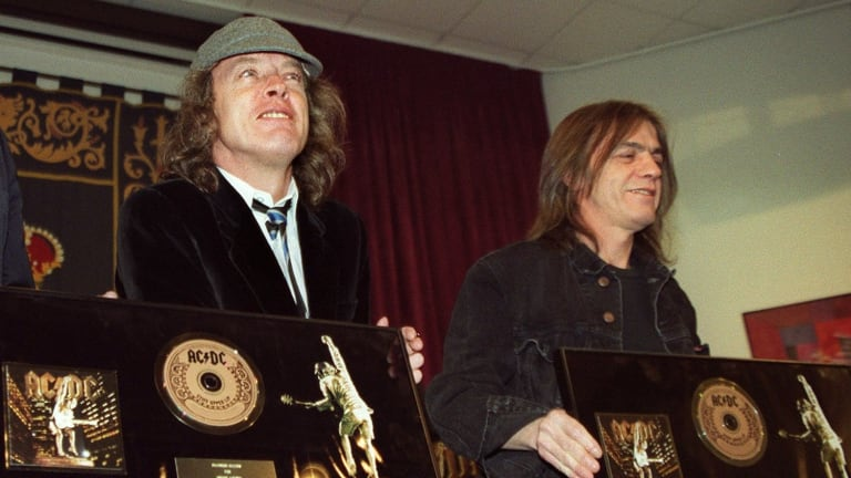 Malcolm Young (right) and fellow AC/DC founder and brother Angus Young pose with a presentation for their album Stiff Upper Lip in Spain in 2000.
