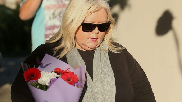 A woman delivers flowers to the Ristevskis' home on Tuesday.
