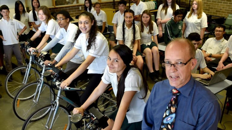 Casula High School science teacher Ken Silburn with students on bikes that produce electricity to power different lights, teaching them about energy use and power consumption.