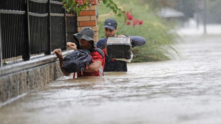 Residents wade through floodwaters in Houston on Sunday.
