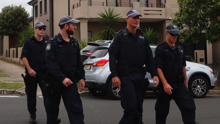 Police officers search for evidence in Merrylands on Saturday.